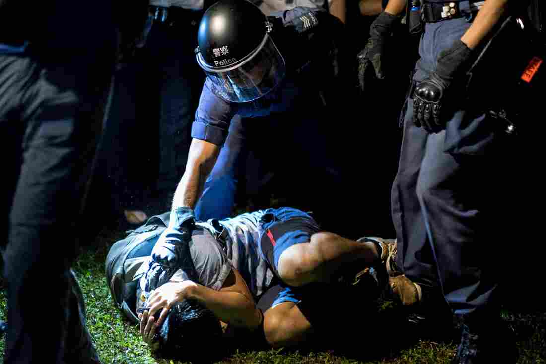 A police officer detains a pro-democracy protester after he was tackled to the ground in Hong Kong.