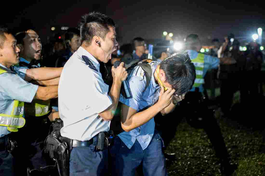 A police officer shouts at a pro-democracy protester after he was hit with pepper spray in Hong Kong on Wednesday.