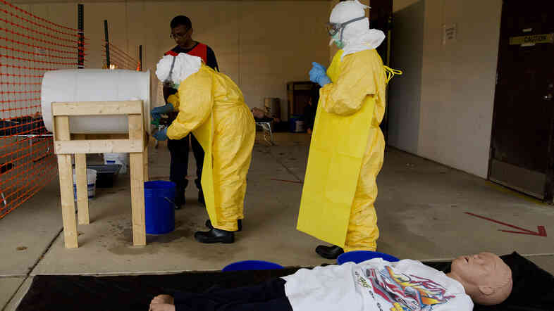 At a CDC training session for clinicians headed to West Africa, a medical worker practices sanitizing hands after drawing blood from a mannequin portraying an Ebola patient.