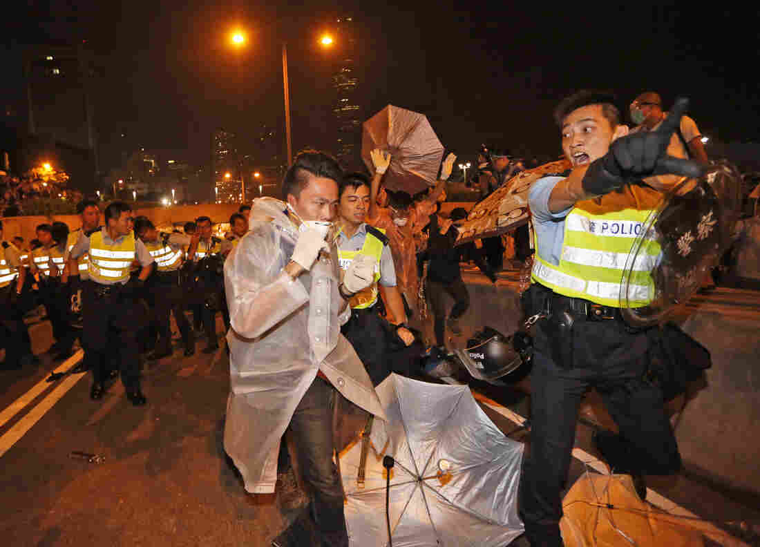 Police officers ask protesters to move to a nearby park outside government headquarters in Hong Kong's Admiralty district.