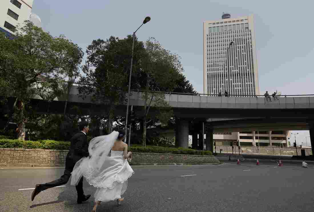 A couple, running late for their wedding ceremony due to the occupation of the main roads by pro-democracy protesters, run towards the marriage registry, in Hong Kong on Tuesday.