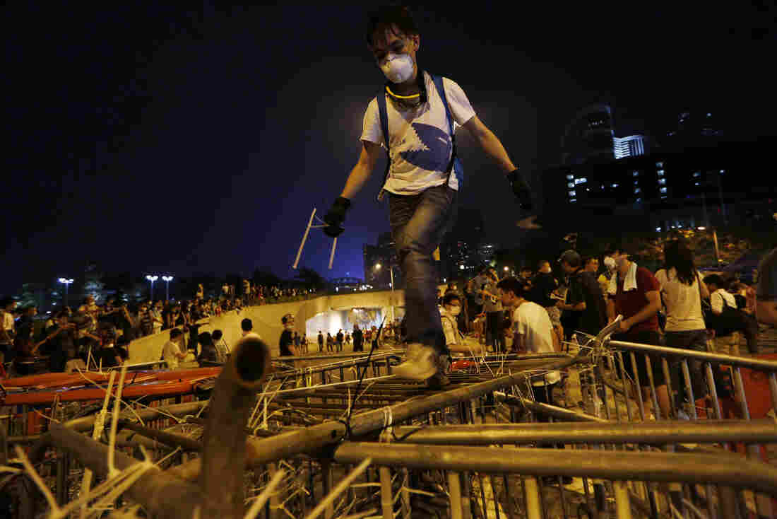 A demonstrator climbs over barriers as others block the main road with metal and plastic safety barriers outside government headquarters in Hong Kong's Admiralty district.