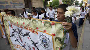 """Students hold a banner with the faces of the missing that reads in Spanish """"Iguala, cradle of murders."""""""