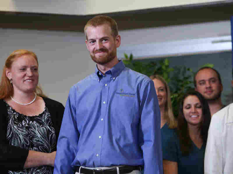 Dr. Kent Brantly (center), stands with his wife, Amber Brantly, during a press conference announcing his release from Emory Hospital on Aug. 21, 2014 in Atlanta, Georgia.