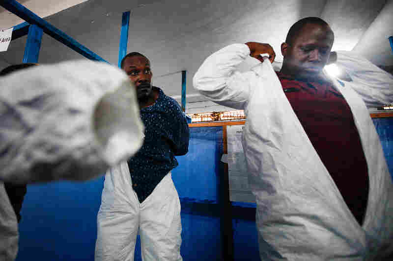 "Eloba trainees, including doctors, nurses and sanitation workers, suit up on their fifth and final day of training and their first ""dress rehearsal"" before being sent out to Ebola treatment units."