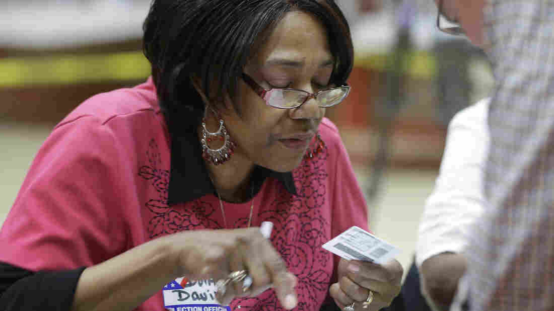 Election worker Dorothy Davis checks a voter's ID during Arkansas' party primary elections in May. After a state Supreme Court ruling, Arkansas' voter ID law won't be in effect for the November elections.