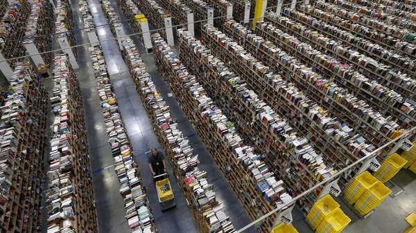 An Amazon.com employee walks down one of the miles of aisles at an Amazon.com Fulfillment Center in Phoenix.