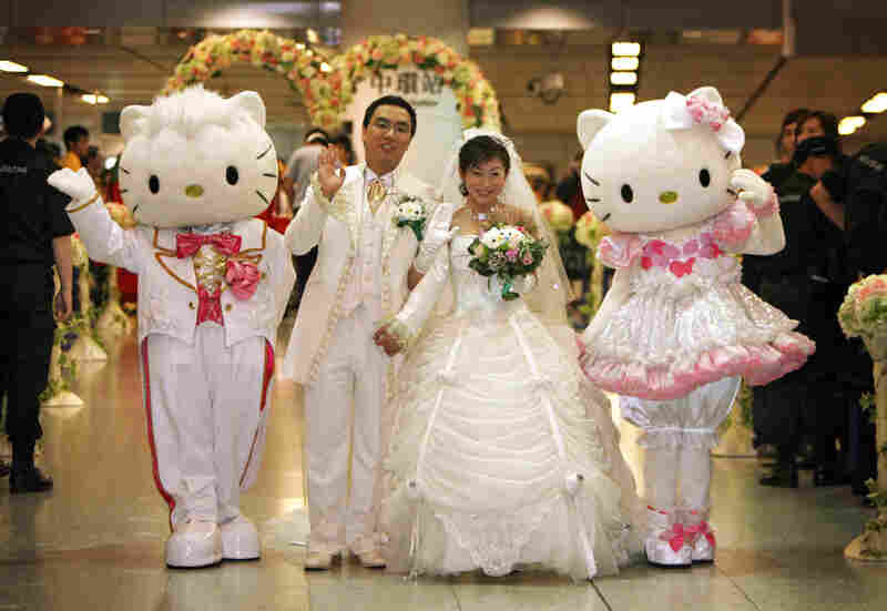 "Jamie Ng (left) and Horlick Ng pose with Hello Kitty and Dear Daniel at Hong Kong's Mass Transit Railway during a ""Hello Kitty Dream Wedding"" in Hong Kong in 2007."