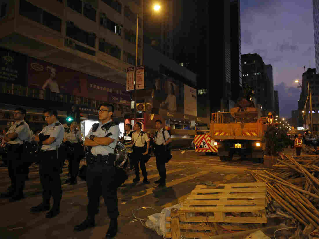 Police officers stand guard at a main street in Mong Kok district in Hong Kong on Friday, where they raided a student protest site.
