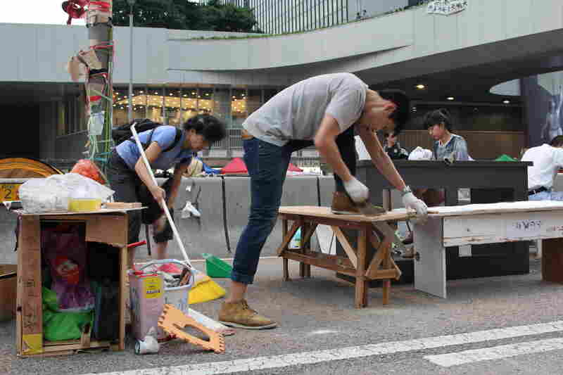 People with no past carpentry experience jump in to build tables and chairs from scrap wood so the students can continue their studies while protesting.