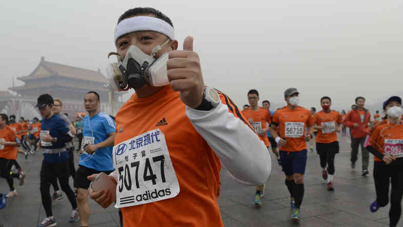 Participants wearing masks during a hazy day at the Beijing International Marathon in front of Tiananmen Square on Sunday.