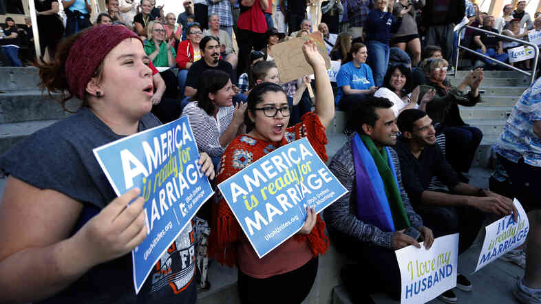 """People hold signs, including some reading """"America is ready for marriage,"""" at a same-sex marriage victory celebration on Oct. 6 in Salt Lake City, Utah. America may be ready, but Republicans aren't: Rising popular support for same-sex marriage is posing a problem for the GOP."""