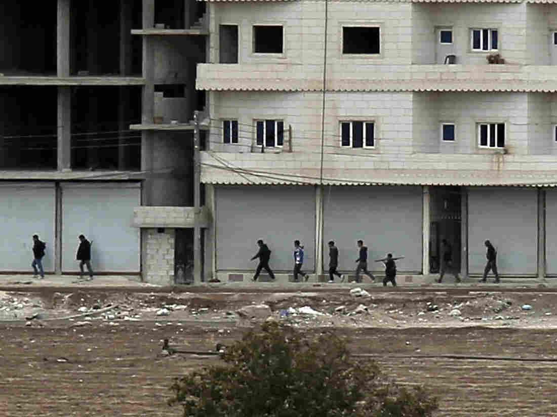 Kurdish fighters move into position in Kobani, Syria on the border with Turkey Sunday, Oct. 19, 2014.