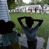 Children watch from their home in Ferguson, Mo., on Aug. 20 as people march about a mile to the police station to protest the shooting of Michael Brown. Brown's shooting in the middle of a street by a Ferguson police officer on Aug. 9 sparked protests, riots and looting in the St. Louis suburb. Some people are ready to leave the troubled city. Others say they will remain no matter what.