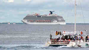 The cruise ship Carnival Magic floats behind a catamaran off Cozumel, Mexico on Oct. 17. The ship skipped a planned stop there Friday, the cruise line says, after Mexican authorities delayed granting permission to dock.