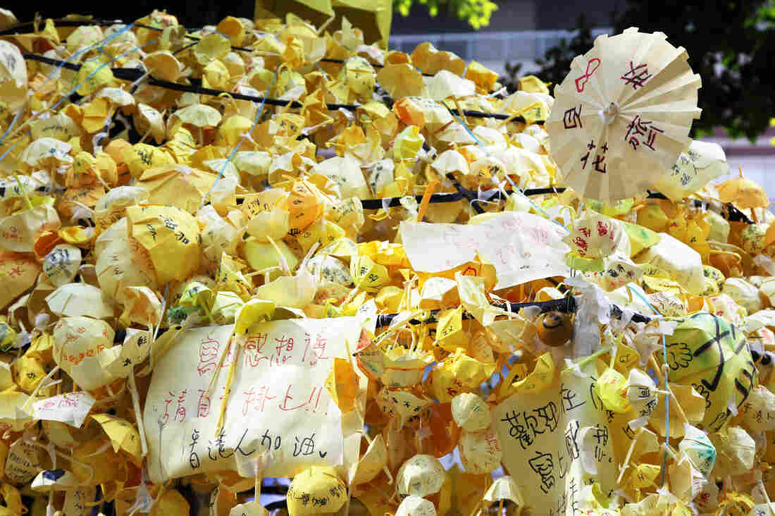 A yellow umbrella made of tiny yellow umbrellas with messages of hope written in Chinese.