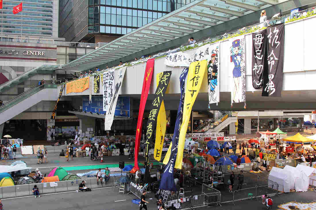 "A pedestrian bridge over the main protest camp in Hong Kong's Admiralty district. The orange banner at the far left says, ""Do You Hear The People Sing?"" the title of a song from Les Miserables, the musical set in 19th-century, revolutionary-era France."