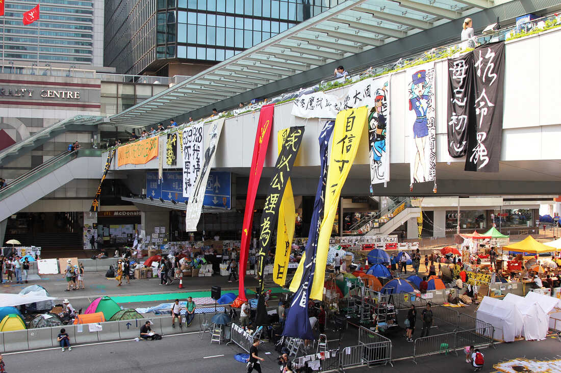 """A pedestrian bridge over the main protest camp in Hong Kong's Admiralty district. The orange banner at the far left says, """"Do You Hear The People Sing?"""" the title of a song from Les Miserables, the musical set in 19th-century, revolutionary-era France."""