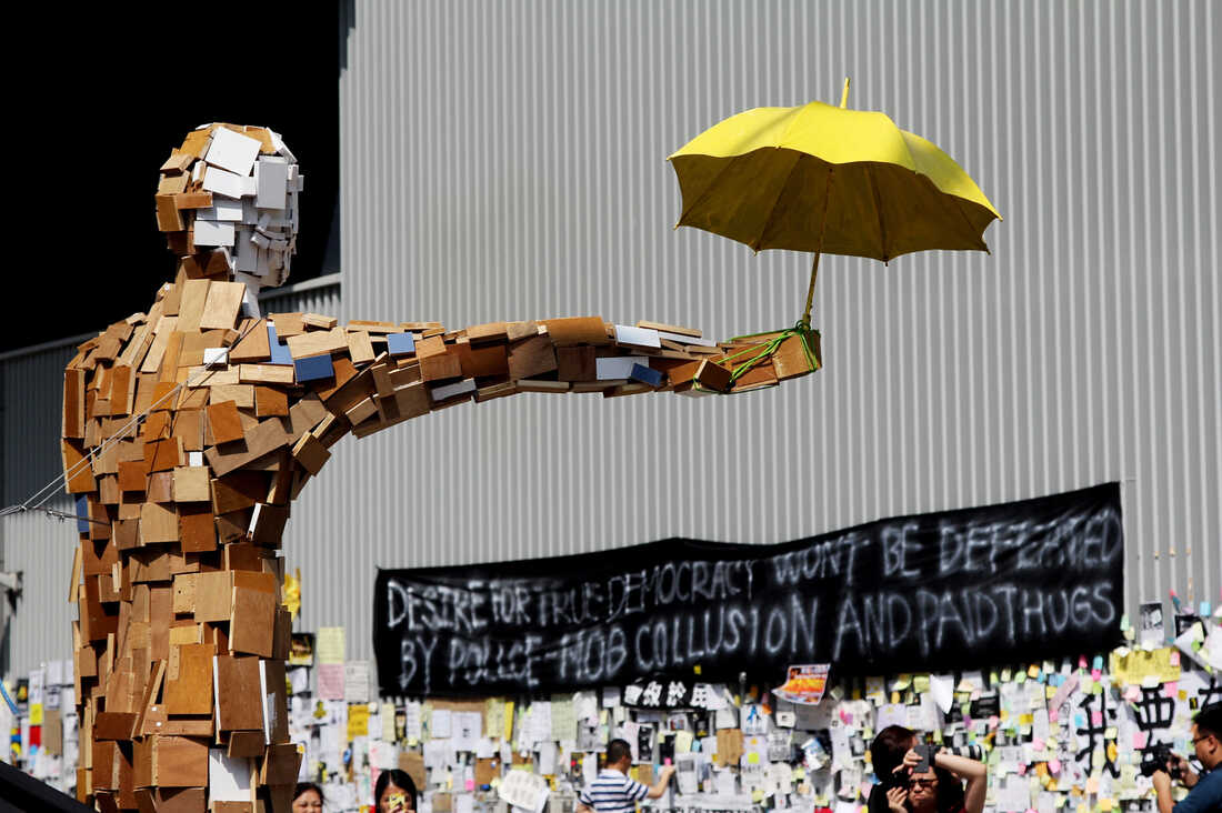 """A scrap-wood sculpture of a man holding an umbrella is the contemporary equivalent of the """"Goddess of Democracy."""" The umbrella became a symbol of the democracy demonstrations after protesters used them to block police pepper spray and tear gas attacks late last month."""