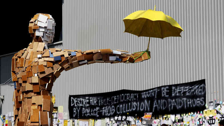 "A scrap-wood sculpture of a man holding an umbrella is the contemporary equivalent of the ""Goddess of Democracy."" The umbrella became a symbol of the democracy demonstrations after protesters used them to block police pepper spray and tear gas attacks late last month."