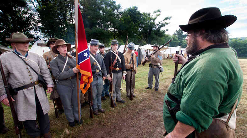 Waverly Adcock, a sergeant and founder of the West Augusta Guard, prepares his company for inspection and battle at a Civil War reenactment in Virginia. Sara Smith, whose great-great grandfather was wounded at the Battle of Gettysburg, holds the Confederate battle flag.