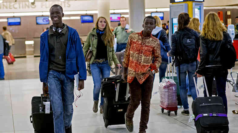 Thomas Nellon (left), 17, and his brother Johnson Nellon, 14, of Liberia smile at their mother in the arrivals area at John F. Kennedy International Airport in New York earlier this month. The brothers received a health screening upon arrival. The U.S. says it will step up screening measures for arrivals from Ebola-affected West African countries.
