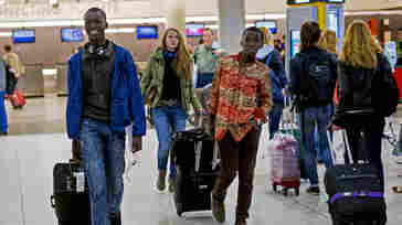 Thomas Nellon, left, 17, and his brother Johnson Nellon, 14, of Liberia, smile at their mother in the arrivals area at John F. Kennedy International Airport in New York, earlier this month. The brothers received a health screening upon arrival. The U.S. says it will step up screening measures for arrivals from Ebola-affected West African countries.