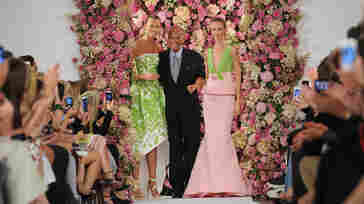 Designer Oscar de la Renta takes a bow with models Karlie Kloss (left) and Daria Strokous after his Spring 2015 collection was modeled Sept. 9 during Fashion Week in New York. De la Renta died on Oct. 20.