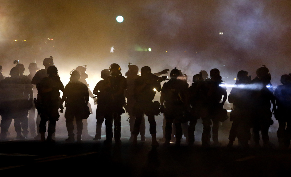 Police walk through a cloud of smoke as they clash with protesters in Ferguson, Mo., this summer. (Jeff Roberson/AP)