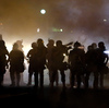 Police walk through a cloud of smoke as they clash with protesters in Ferguson, Mo., this summer.