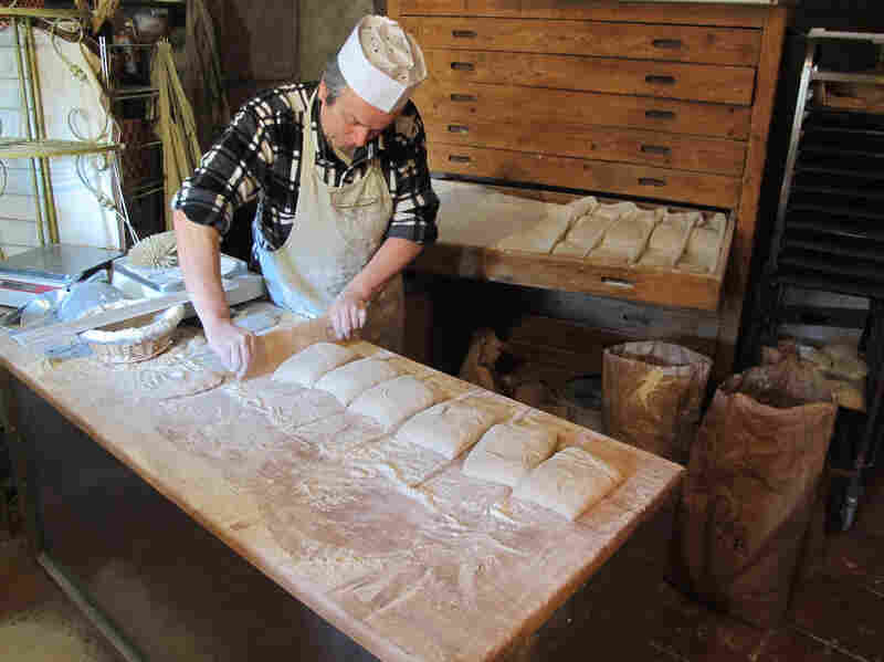 """Roland Feuillas of Cucugnan, France, is """"among a small movement paysannes boulangers (peasant bakers) who grow their own organic wheat, mill it into flour and make their bread,"""" Fromartz writes. Here, Feuillas shapes loaves with a single cut."""
