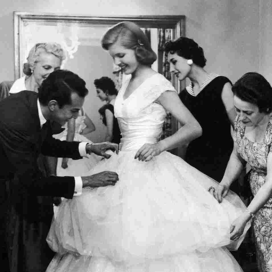 Baroness Aino Bodisco (far right) looks on as Beatrice Lodge is fitted in a debutante dress by fashion designer Oscar de la Renta in 1956.