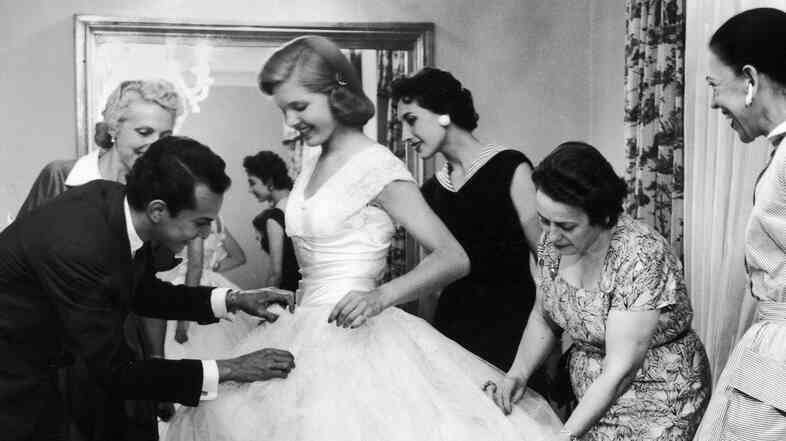 Baroness Aino Bodisco (far right) looks on as Beatrice Lodge is fitted in a debutante dress by fashion designer Oscar de la Renta in 1956.