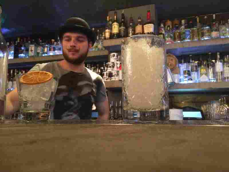 A bartender at Graphic works on drinks for NPR reporter Ari Shapiro and producer Rich Preston.