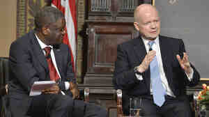 Dr. Denis Mukwege (left) listens as Britain's Foreign Secretary William Hague speaks after the two men were presented Georgetown University's annual Hillary Rodham Clinton Award for Advancing Women in Peace and Security, at Georgetown University in Washington, in February.