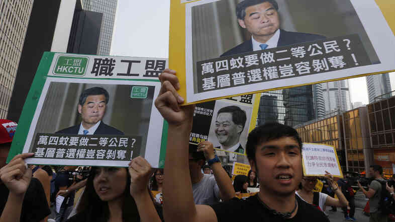 Pro-democracy protesters carrying portraits of Hong Kong Chief Executive Leung Chun-ying march to his residence in Hong Kong on Wednesday.