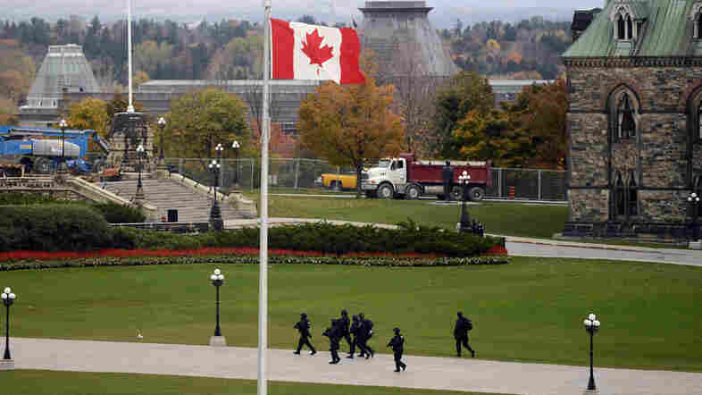 Law enforcement officers scour Parliament Hill grounds in Ottawa after a shooting incident Wednesday.