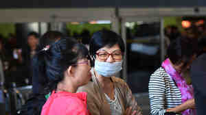 A passenger wearing a face mask arrives at Los Angeles International Airport Friday. Federal officials now require people traveling from West Africa to enter the U.S. at one of five airports equipped to screen them for signs of Ebola.