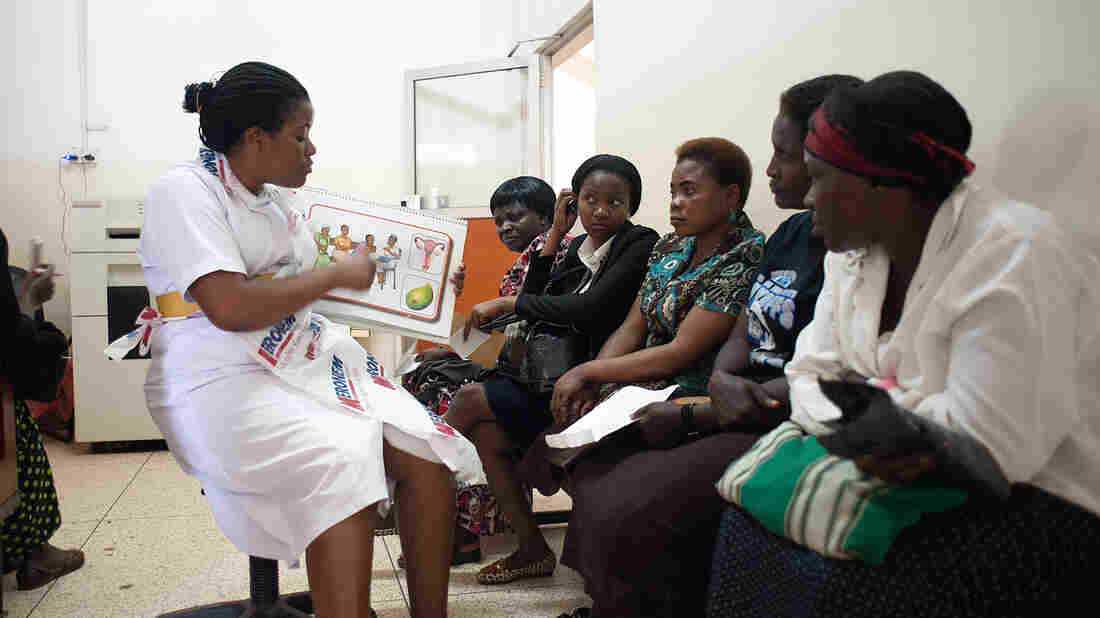 A nurse uses a diagram of the female reproductive system to explain the do-it-yourself careHPV test at the Uganda Cancer Institute in Kampala.