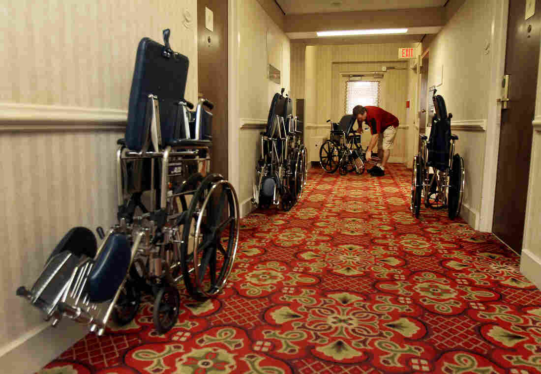 Mayo Clinic employee Kevin Acker collects wheelchairs from a hallway at the Kahler Grand Hotel in Rochester. He retrieves abandoned chairs around the city every weekend.