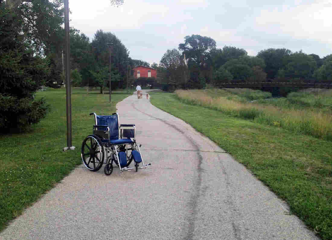 A lone Mayo Clinic wheelchair sits on the Cascade Creek walking trail near Kutzky Park in Rochester, Minn.