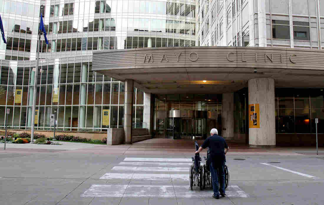 Mayo Clinic employee Merle Paxton returns wheelchairs to a building on campus.