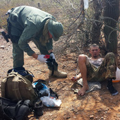 An unidentified U.S. Border Patrol agent, left, helps an immigrant, including setting up intravenous fluid replacement for dehydration, near Sells, Ariz. on June 25.