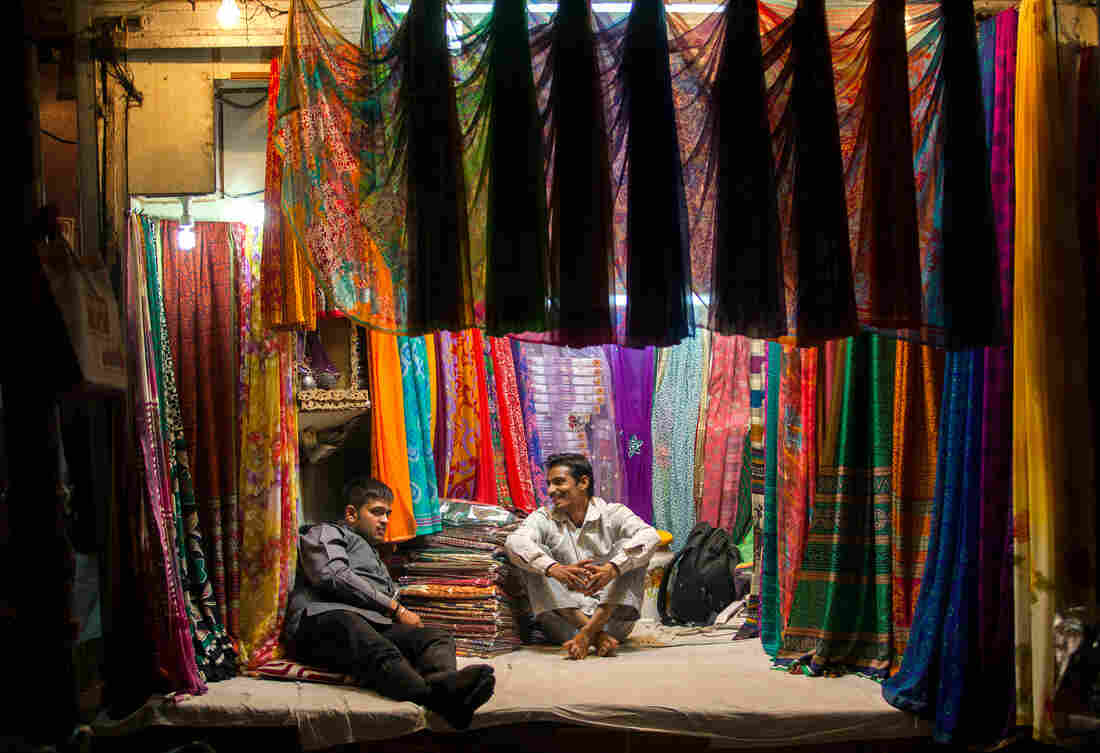 Indian sari vendors share a light moment in the Old Quarters in New Delhi in 2013.