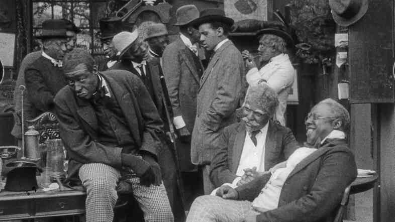 Scene still from Bert Williams Lime Kiln Field Day Project. Bert Williams, Walker Thompson (standing center), John Wesley Jenkins (seated right). In a concession to white audiences, Williams, the lead, wore blackface, but the other black characters did not.
