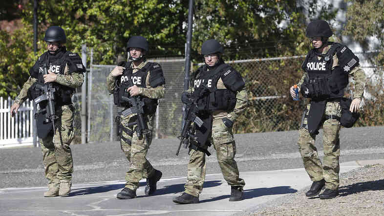 Law enforcement officers dressed in tactical gear leave the Gold County Fairgrounds to help in the search of an assailant, in Auburn, Calif., who shot three sheriff's deputies in two Northern California Counties, on Friday.