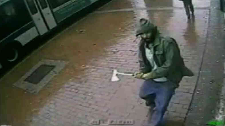 In this frame grab taken from video provided by the New York Police Department, an unidentified man approaches New York City police officers with a hatchet, on Thursday. The man was fatally shot by police after he wounded two officers.