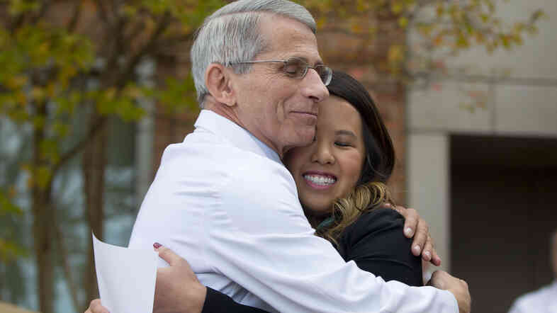 Patient Nina Pham is hugged by Dr. Anthony Fauci, director of the National Institute of Allergy and Infectious Diseases, outside of the National Institutes of Health in Bethesda, Md., on Friday. Pham was discharged after testing free of Ebola.