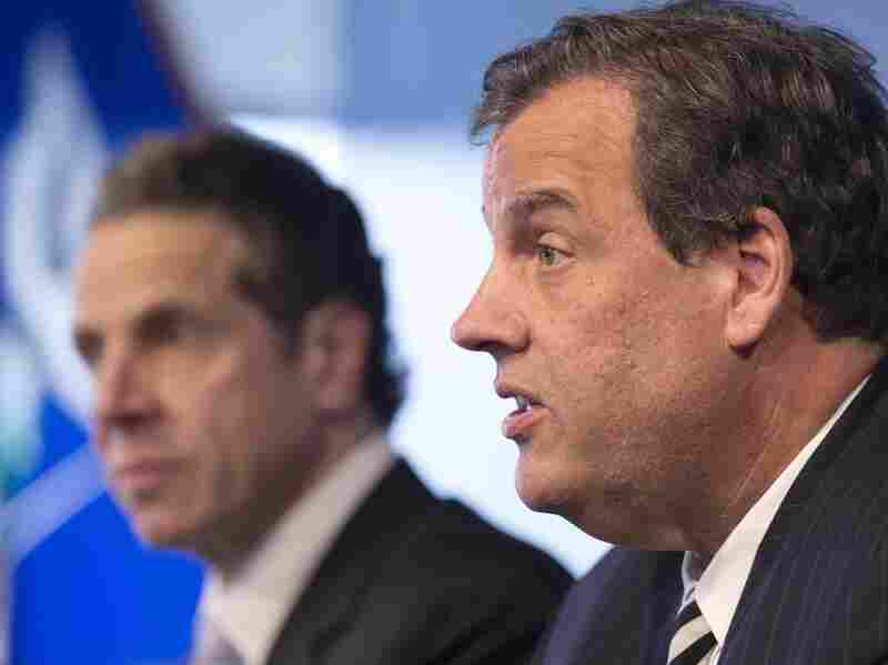 """New York Gov. Andrew Cuomo, left, listens Friday as New Jersey Gov. Chris Christie talks at a news conference in New York. The governors announced a mandatory quarantine for people returning to the United States through airports in New York and New Jersey who are deemed to be at """"high risk"""" for Ebola."""