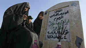 The family of Ibrahim Abid, who was killed when guards employed by security company Blackwater opened fire at Baghdad's Nisour Square in 2007, visits his grave on Dec. 9, 2008.